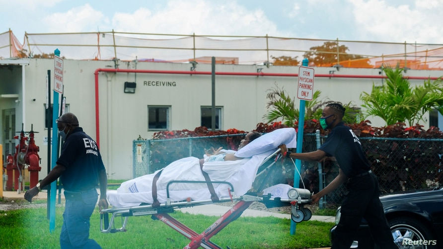 Emergency Medical Technicians (EMT) leave with a patient at North Shore Medical Center where the coronavirus disease (COVID-19) patients are treated, in Miami