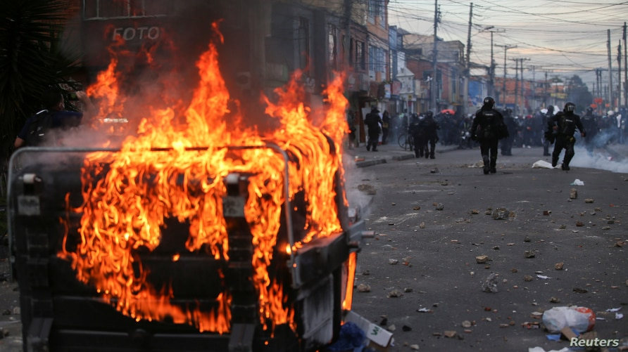 A garbage container burns during protests after a man, who was detained for violating social distancing rules, died from being repeatedly shocked with a stun gun by officers, according to authorities, in Bogota