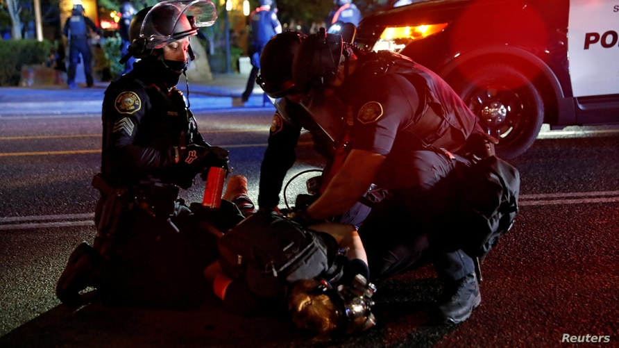 FILE PHOTO: Police officers detain a demonstrator during a protest against police violence and racial injustice in Portland