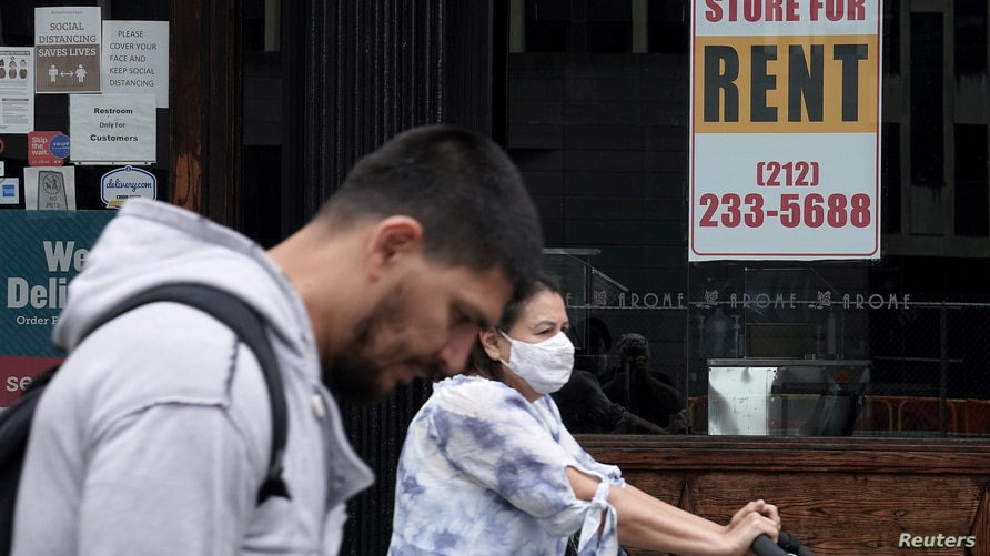 People walk past a shuttered store in New York City