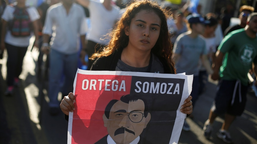 FILE PHOTO: A demonstrator holds a sign showing Nicaraguan President Daniel Ortega and former President Anastasio Somoza during a protest against police violence and the government of President Ortega in Managua