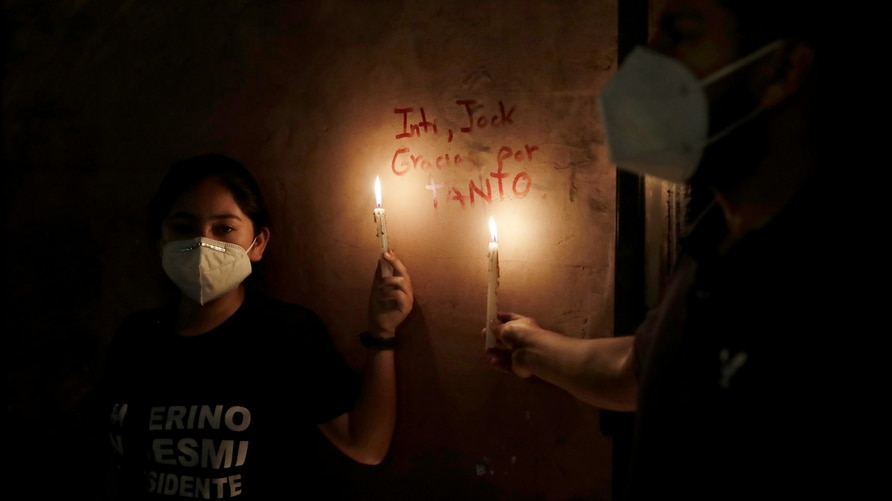 Women hold candles next to the names of two people who were killed in clashes during protests following the ouster of President Martin Vizcarra, in Lima
