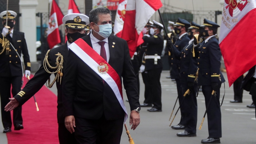 Peru's interim President Manuel Merino reviews an honour guard after he was sworn in following the removal of President Martin Vizcarra by lawmakers, in Lima