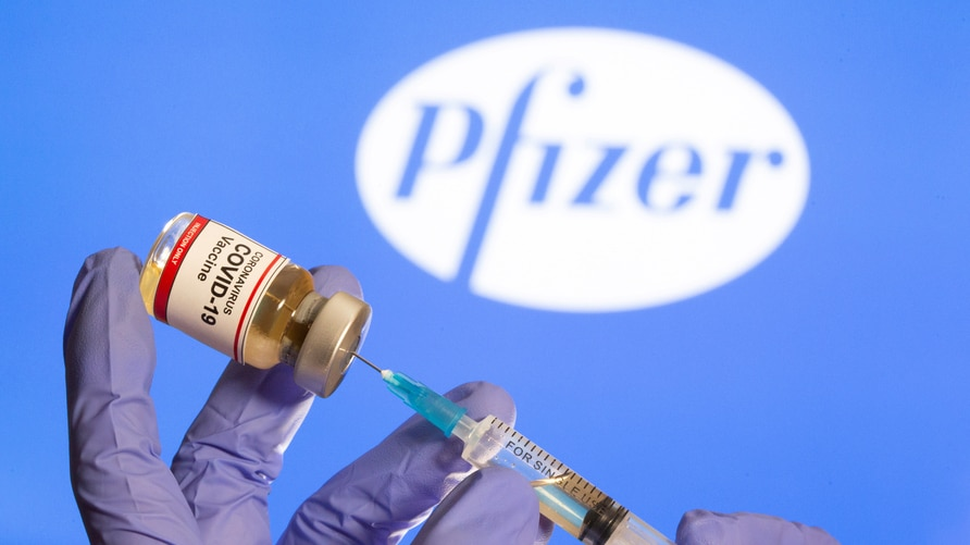 "FILE PHOTO: A woman holds a small bottle labeled with a ""Coronavirus COVID-19 Vaccine"" sticker and a medical syringe in front of displayed Pfizer logo in this illustration"