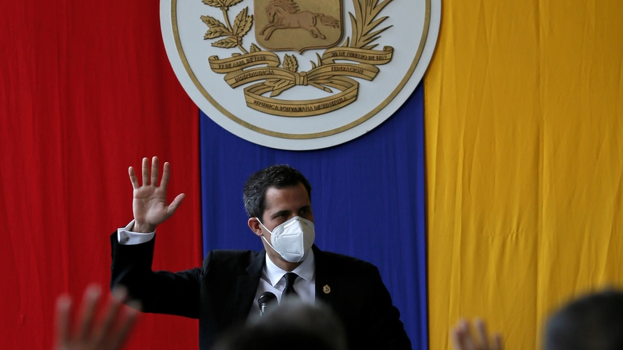 Venezuela's opposition leader Juan Guaido raises his hand during a session of Venezuela's National Assembly at a public park in Caracas