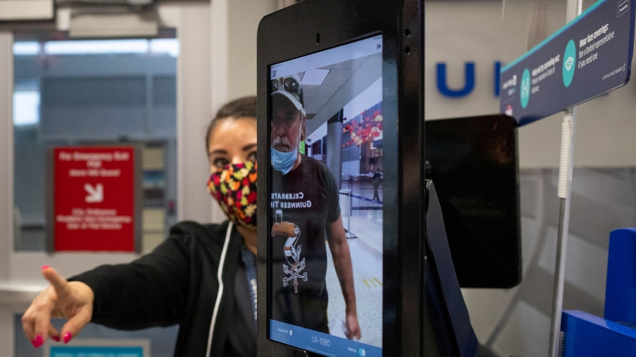 FILE PHOTO: United Airlines employee positions a traveler using biometric boarding at IAH airport in Houston