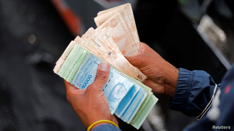 A bus driver's assistant counts a wad of Bolivar banknotes at a bus stop outside the Antimano metro station in Caracas