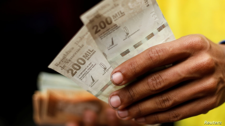 The assistant of a bus driver holds banknotes of 200,000 bolivars, worth just 10 U.S. cents at the current exchange rate, in Caracas