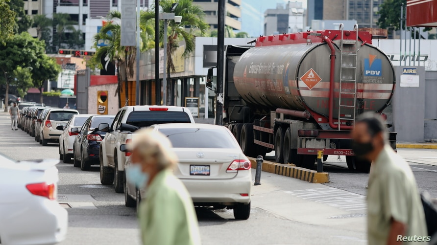 FILE PHOTO: A gas truck is seen next to a line of cars in front of a gas station in Caracas