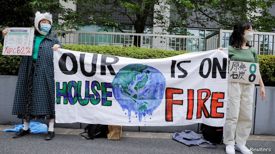 Young climate activists attend a rally calling on policy makers to raise the target of greenhouse gas reduction to mark the World Earth Day in Tokyo