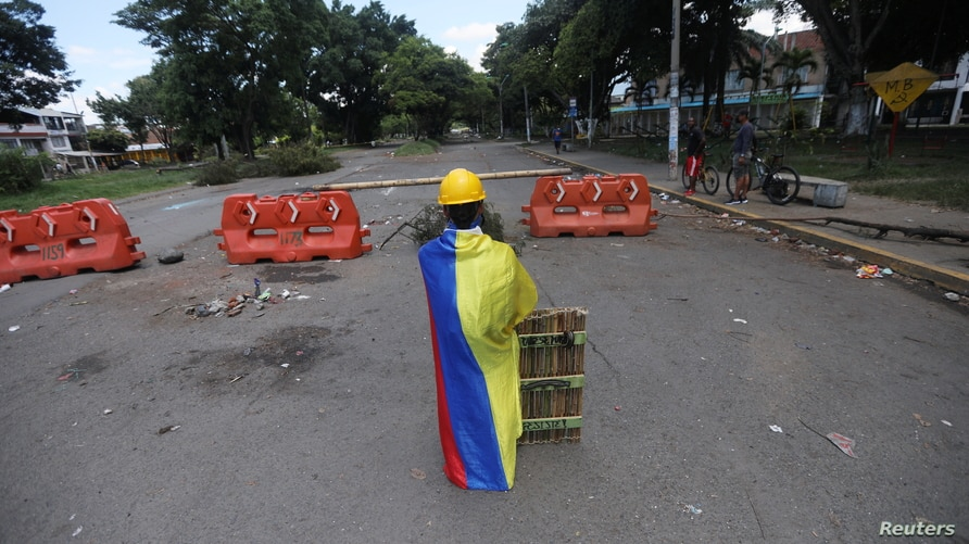A front-line demonstrator draped in a Colombian flag poses for a photo at a barricade in Cali