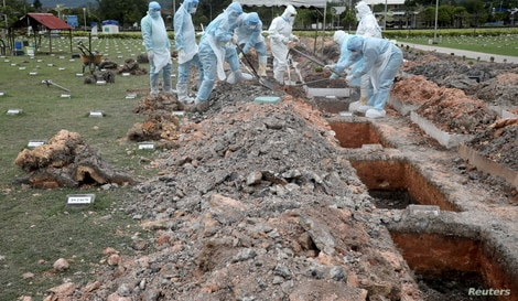 Workers wearing protective suits bury a victim of the coronavirus disease (COVID-19) at a cemetery, in Batu Caves, Malaysia…