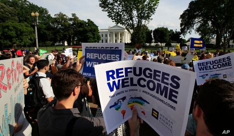 Refugees and community activists gather in front of the White House in Washington, Tuesday, June 20, 2017, during a rally in…