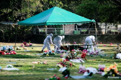 Gravediggers wear protective clothing while burying a person who died during the outbreak of the coronavirus disease (COVID-19)…