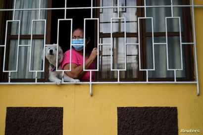 A resident observes municipality healthcare workers going house-to-house as they conduct contact tracing amid the coronavirus…