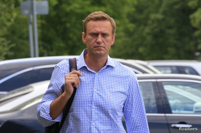 FILE PHOTO: Russian opposition leader Alexei Navalny, who is charged with participation in an unauthorised protest rally, walks…