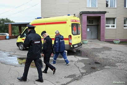 A medical worker and police officers walk outside the City Clinical Emergency Hospital Number 1 where Russian opposition leader…