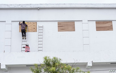 Workers board up the windows of a store in preparation for hurricane Nana -expected as a Category 1 hurricane with winds up to…