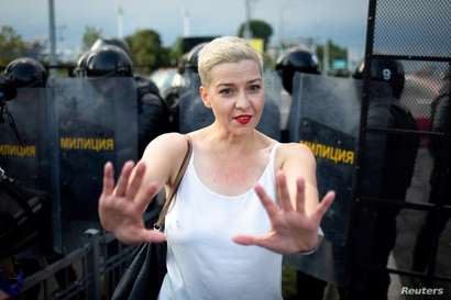 Belarusian opposition politician Maria Kolesnikova gestures in front of law enforcement officers during a rally in Minsk,…
