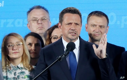 A top candidate in Poland's presidential election, Warsaw Mayor Rafal Trzaskowski, front, reacts to the exit poll after voting…