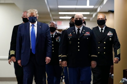 President Donald Trump wears a face mask as he walks down a hallway during a visit to Walter Reed National Military Medical…