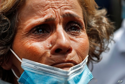 A Lebanese woman whose son is missing after the explosion Tuesday that hit the seaport of Beirut, cries as she waits outside…