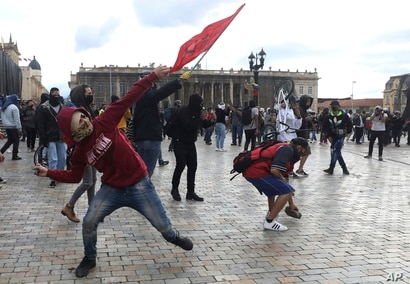 Demonstrators hurl stones at the police during clashes in Bogota, Colombia, Monday, Sept. 21, 2020. Unions and student groups…