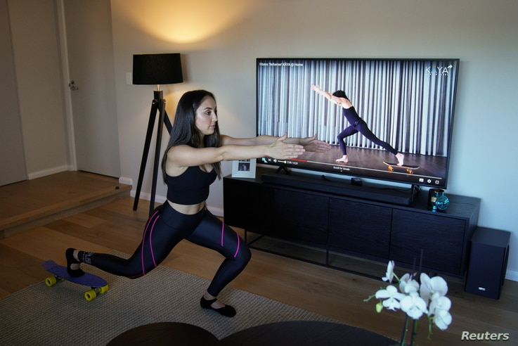 Sydney resident Alexandra Gallo uses a guided skateboard Pilates class found online to exercise inside her home, as the Pilates…