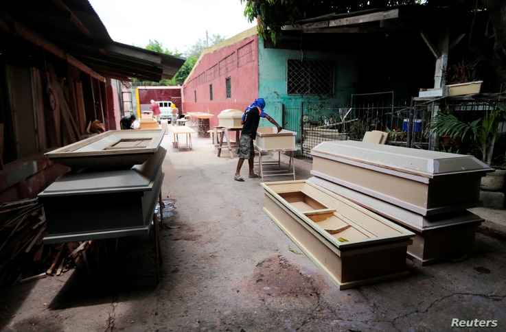 An employee works in the making of coffins at a workshop inside a funeral complex amid the coronavirus disease (COVID-19)…
