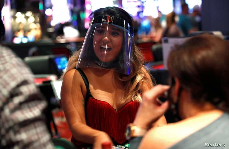 A blackjack dealer wears a face shield during the reopening of The D hotel-casino, closed by the state since March 18, 2020 as…