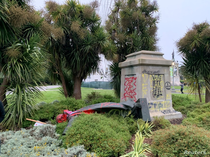 St Junipero Serra statue faces the ground memorial after being vandalised with red spray paint in San Francisco, California, U…