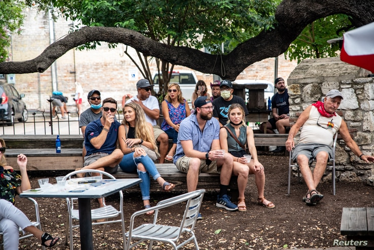 People sit at an outdoor bar and eating area amid the global outbreak of the coronavirus disease (COVID-19), in Austin, Texas,…