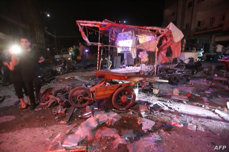 People gather at the site of an air strike on a market in the town of Maaret al-Numan on May 21, 2019. - At least 12 people…