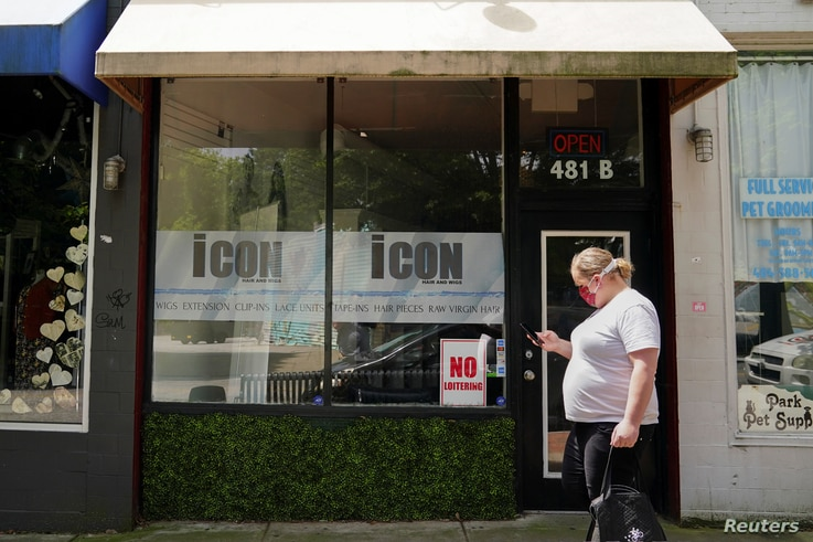 A woman carrying a Postmates delivery bag passes by a hair salon and wig shop days before the phased reopening of businesses…
