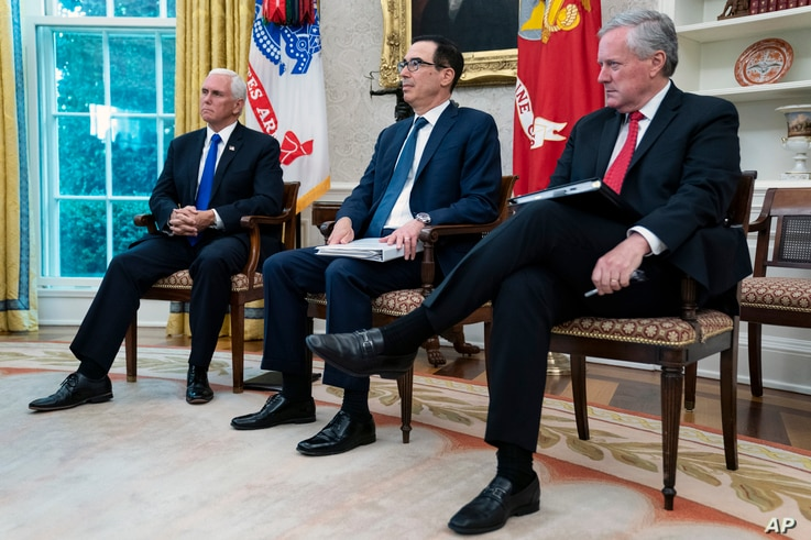 Vice President Mike Pence, left, Treasury Secretary Steven Mnuchin, center, and White House chief of staff Mark Meadows listen…