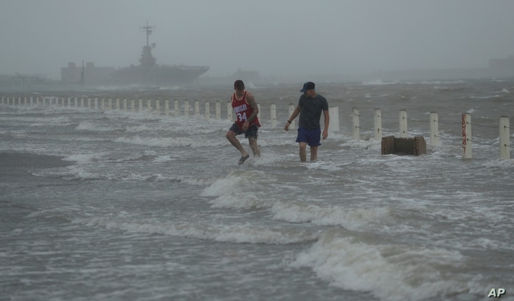 Two men walk on a flooded road as Hurricane Hanna makes landfall, Saturday, July 25, 2020, in Corpus Christi, Texas.   The…