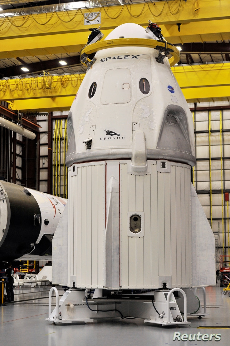 The Dragon crew capsule sits in the SpaceX hangar at Launch Complex 39-A, where the space ship and Falcon 9 booster rocket are…