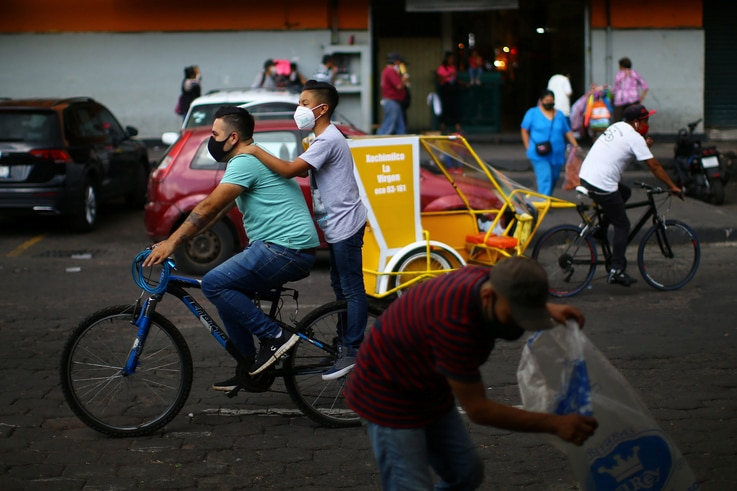 Two youth wearing face masks ride on a bycicle as the coronavirus disease (COVID-19) outbreak continues, in Xochimilco, Mexico…