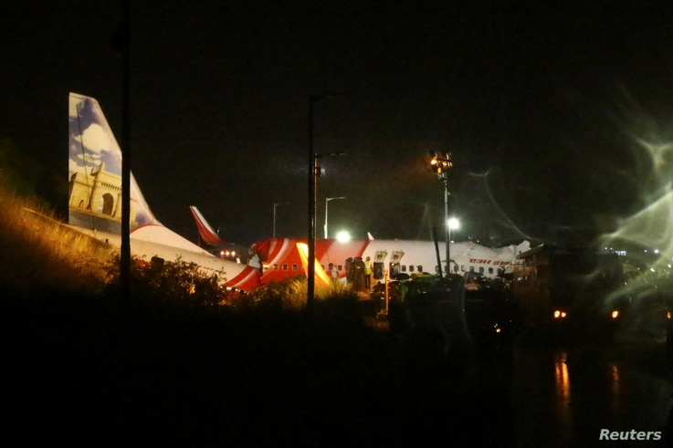 Rescue workers look for survivors after a passenger plane crashed when it overshot the runway at the Calicut International…