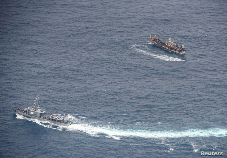 Ecuadorian Navy vessels surround a fishing boat after detecting a fishing fleet of mostly Chinese-flagged ships in an…