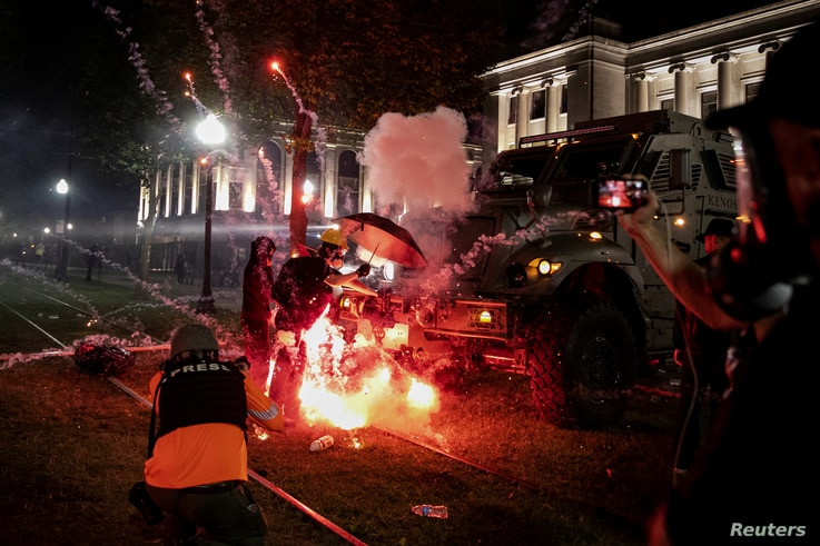 An incendiary device goes off in front of a Kenosha Country Sheriff Vehicle as demonstrators take part in a protest following…