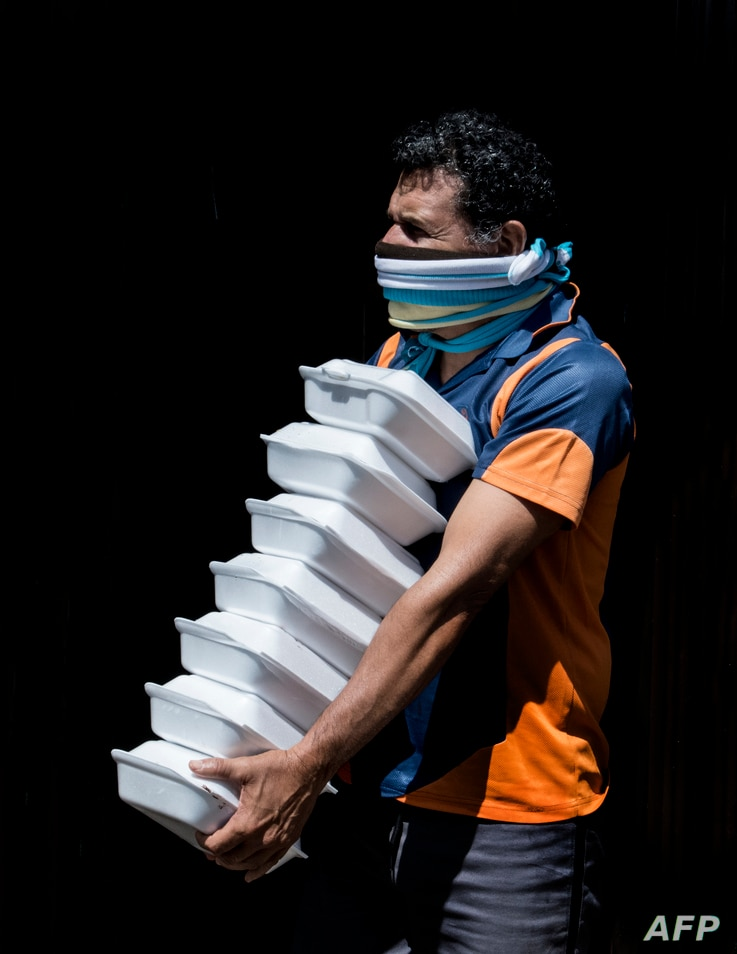A man receives food at a house quarantined due to the COVID-19 pandemic in San Jose, Costa Rica on July 17, 2020. - Most people…