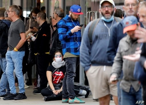 People, some wearing face masks or coverings due to the COVID-19 pandemic, queue to enter The Rolling Stones new flagship store…