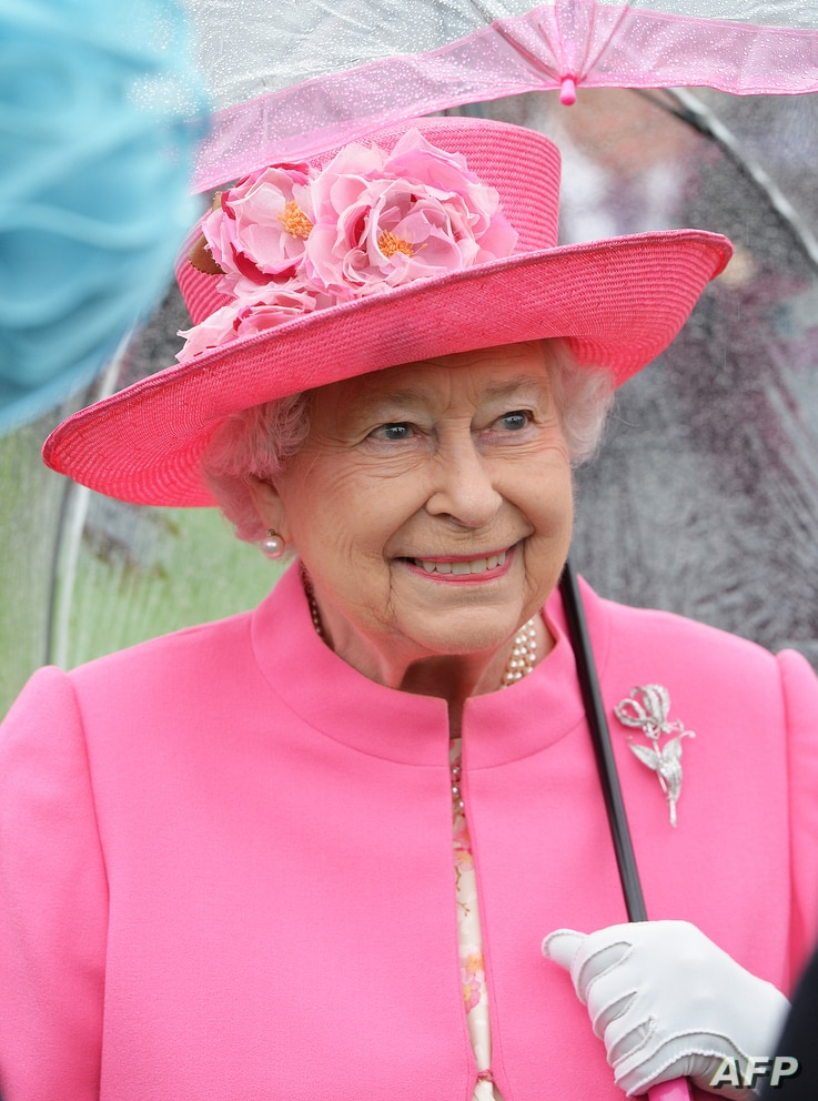 (FILES) In this file photo Britain's Queen Elizabeth II speaks to guests in the garden of Buckingham Palace in London as up to…