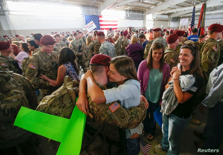 John Jacoby, a paratrooper with the 1st Brigade Combat Team, 82nd Airborne Division, hugs his girlfriend Emiliee Chance after…