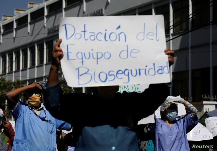 """Health workers hold a sign reading """"Supply biosecurity equipment"""" during a protest outside a hospital as they demand higher…"""