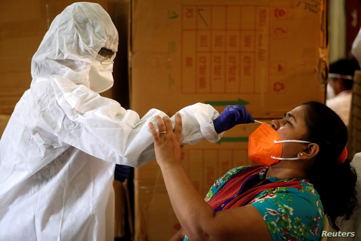 A health worker in personal protective equipment (PPE) collects a swab sample from a woman during a rapid antigen testing…