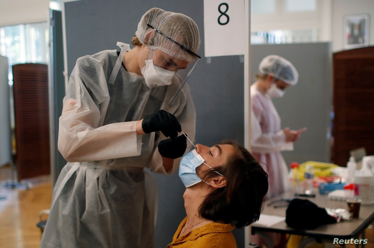 A health worker, wearing a protective suit and a face mask, administers a nasal swab to a patient at a testing site for the…