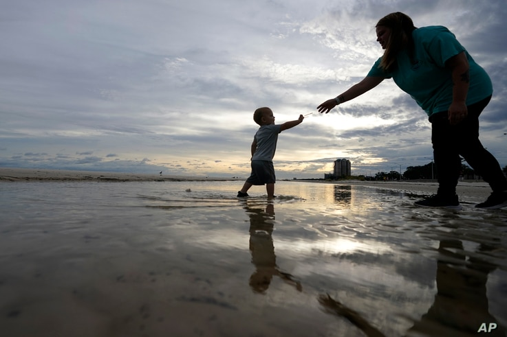 Nikita Pero of Gulfport, Miss., walks with her son Vinny Pero, 2, on the beach along the Gulf of Mexico in Biloxi, Miss.,…