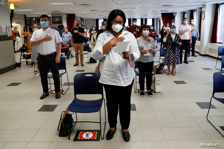 Ifeoma Eh, a citizen candidate from Nigeria, stands with others socially distanced and wearing protective face masks, as the…